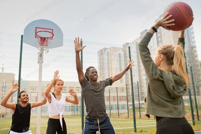 Group of intercultural students or friends in sportswear playing basketball