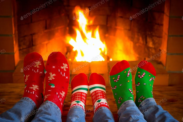 Family in Christmas socks near fireplace