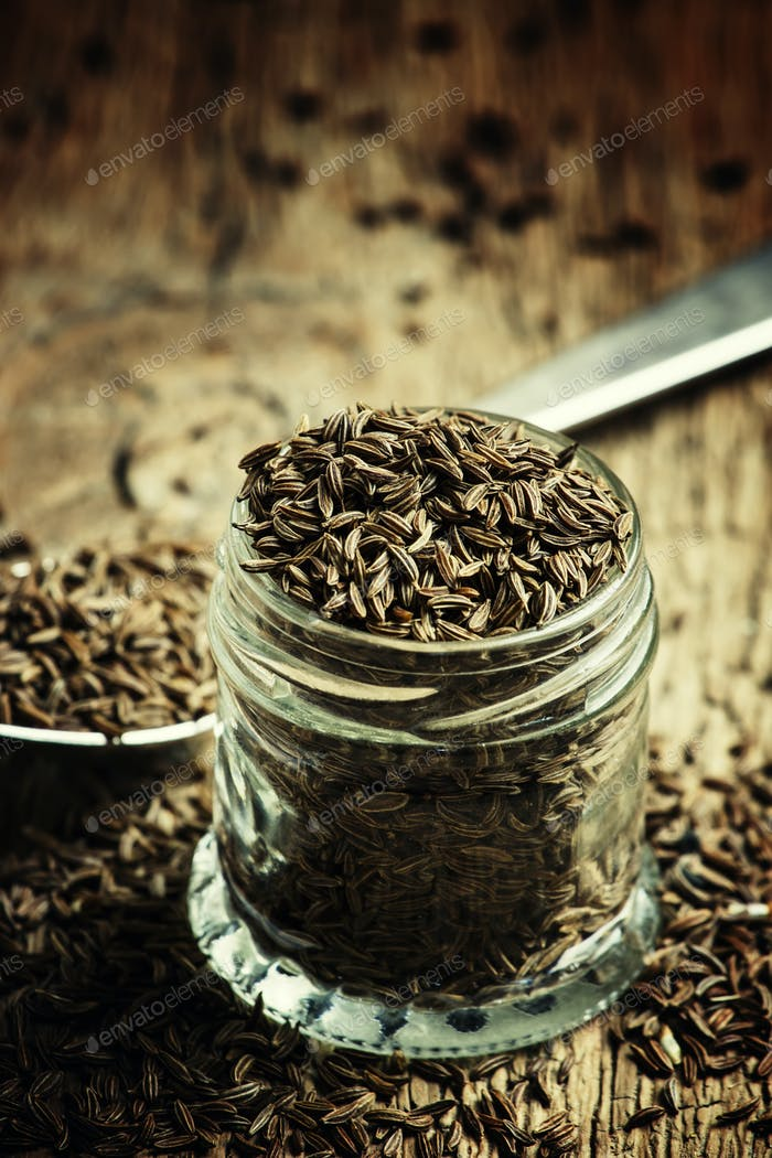 Caraway seeds in a glass jar and a silver spoon