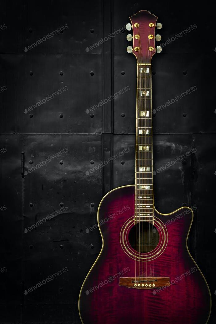 Purple acoustic guitar over dark background