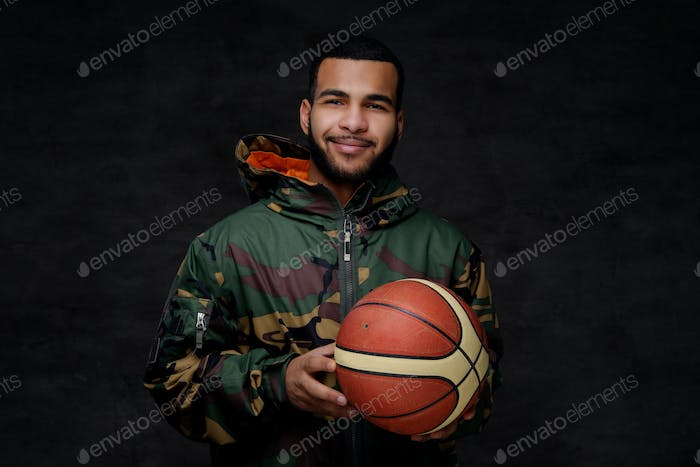 Happy young African-American street basketball player in a camouflage jacket.