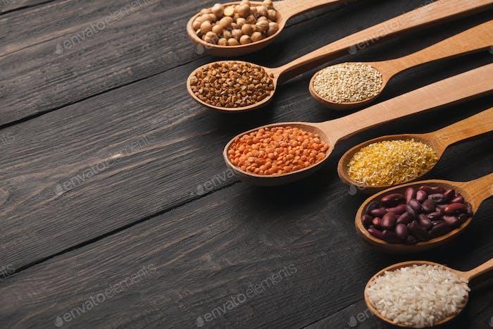 Verschiedene glutenfreie Grütze auf Holzhintergrund, Kopierraum