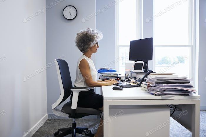 Mittelalter Geschäftsfrau mit Laptop-Computer in ihrem Büro