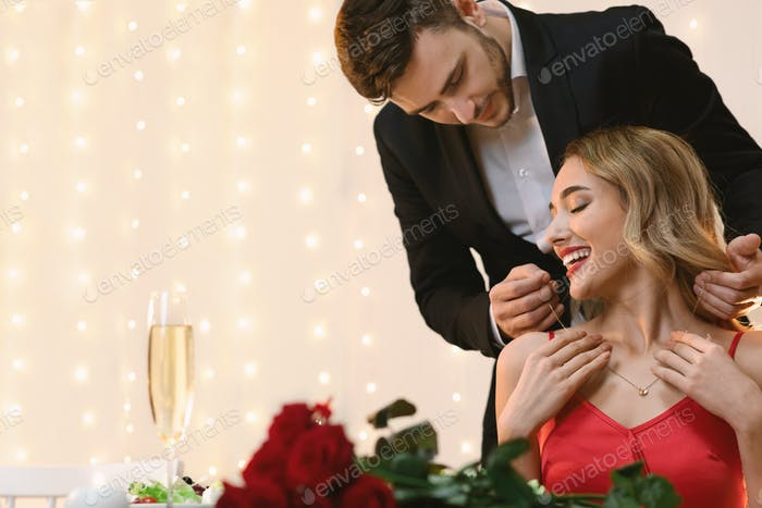 Affectionate Man Presenting Golden Necklace To His Girlfriend At Romantic Dinner
