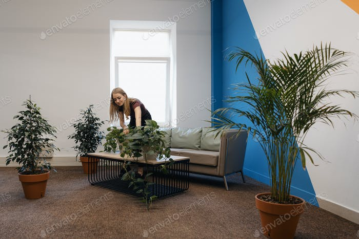 Young female gardening in the office