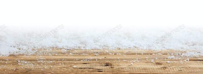 Winter snowy bokeh background over wooden surface