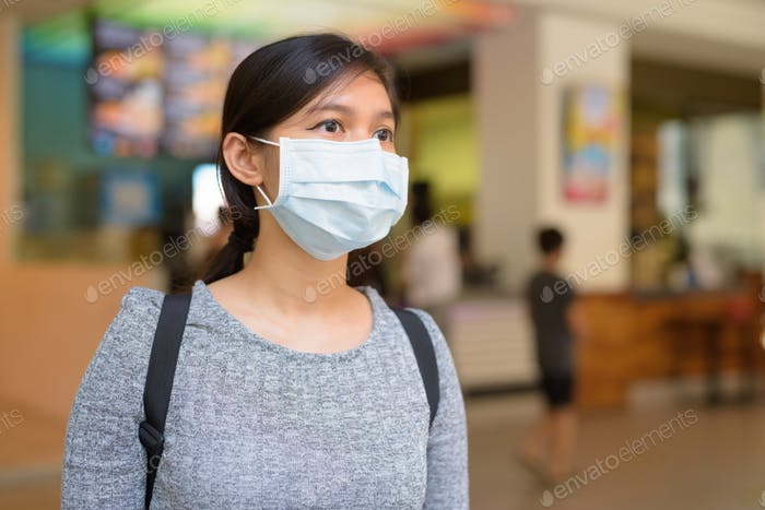 Young Asian woman with mask for protection from corona virus outbreak inside the restaurant