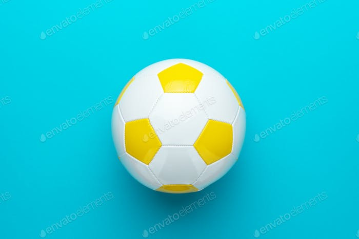 Close-Up Of White And Yellow Soccer Ball In Centre Of Turquoise Blue Background