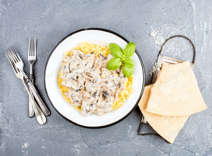 Tagliatelle pasta with mushrooms and creamy sauce, parmesan cheese over concrete textured background