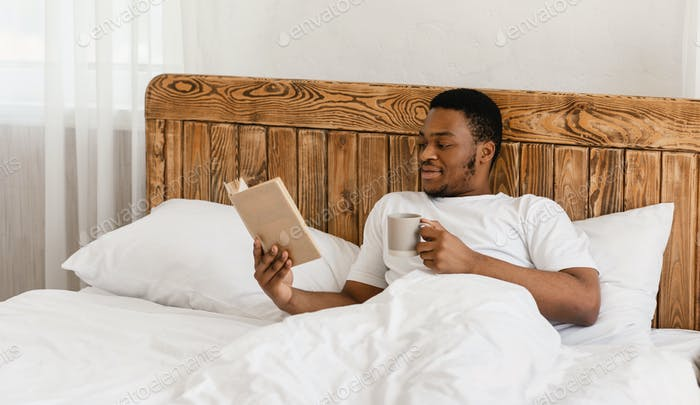 Black Millennial Guy Reading Book Drinking Coffee Lying In Bed