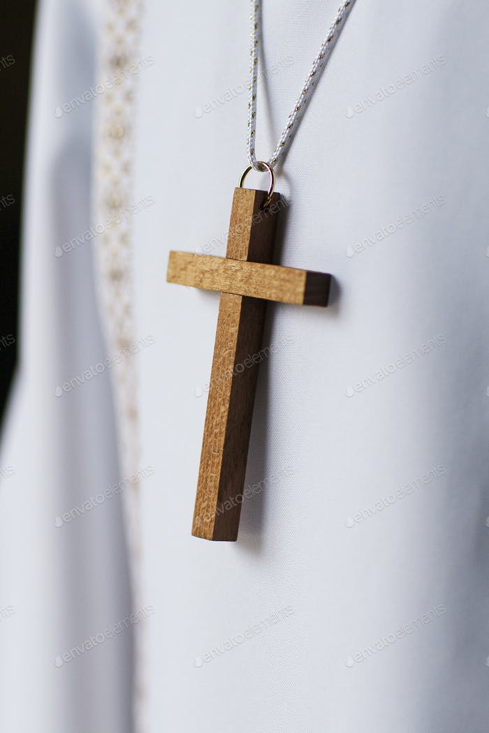 detail of a wooden cross of a child about to receive the first communion