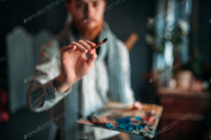 Painter with brush in hand selective focus