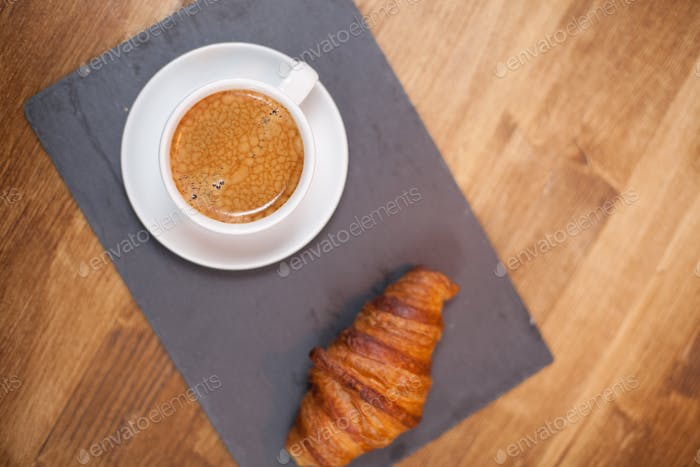 Top view of coffee cup with golden croissant on stone plate