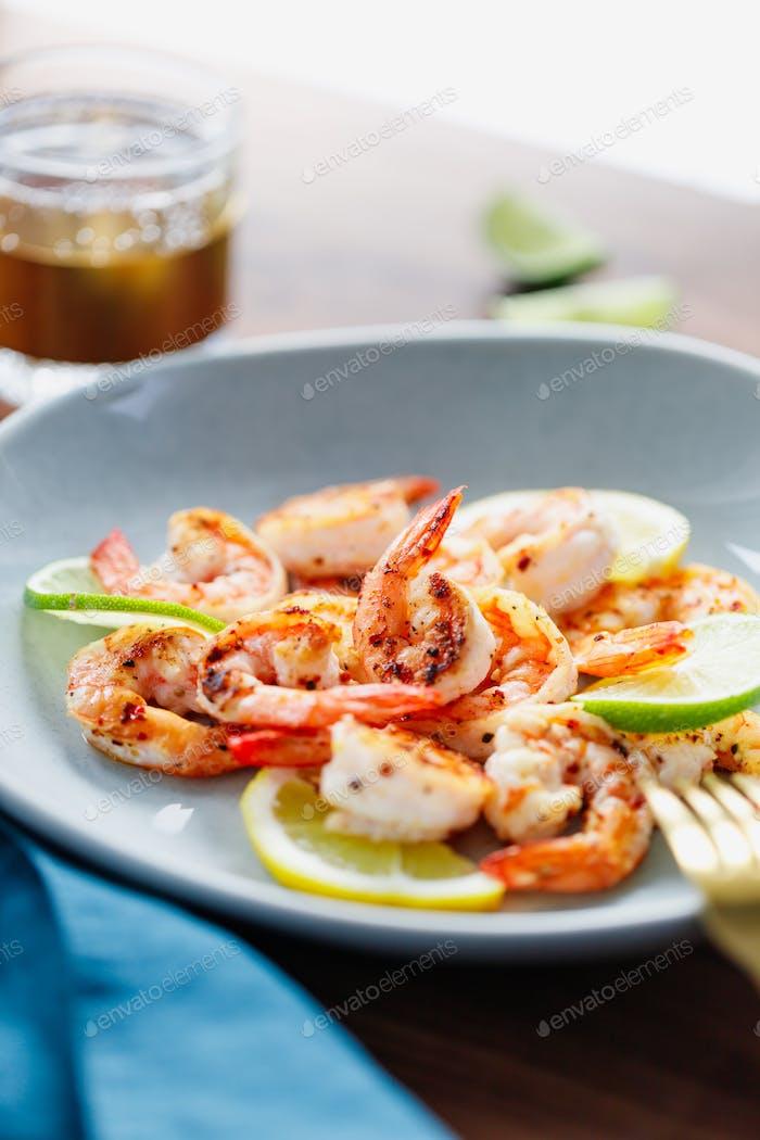 Жареные тигровые креветки с лаймом, лимоном и специями на керамическом блюде. Здоровый ужин или обед концепция.