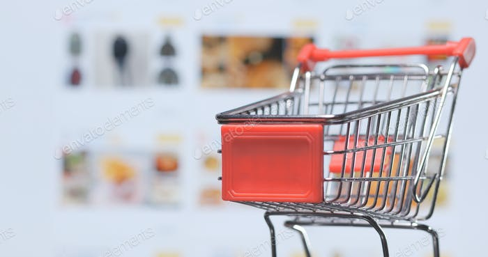 Shopping online concept, small cart over shopping online website