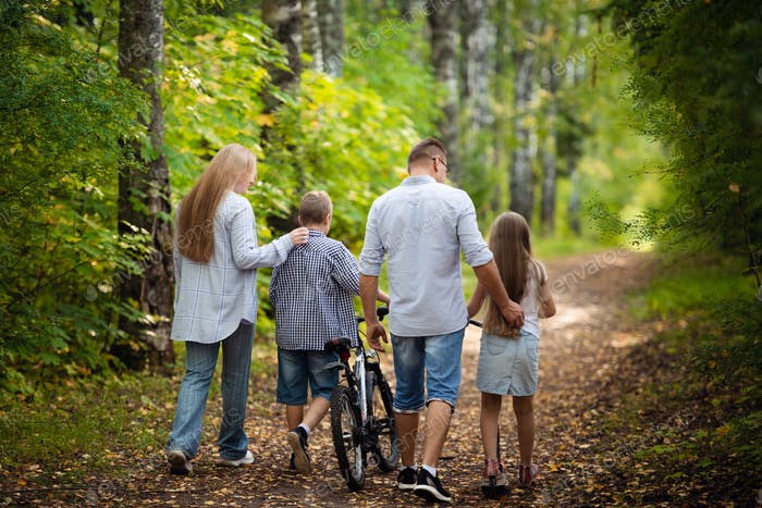 Happy family outdoors spending time together. Father, mother, daughter and son are having fun in a