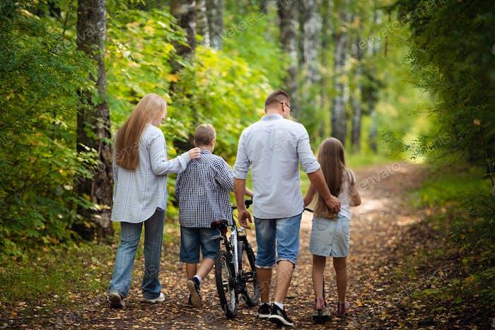 Glückliche Familie im Freien verbringen Zeit zusammen. Vater, Mutter, Tochter und Sohn haben Spaß in einem