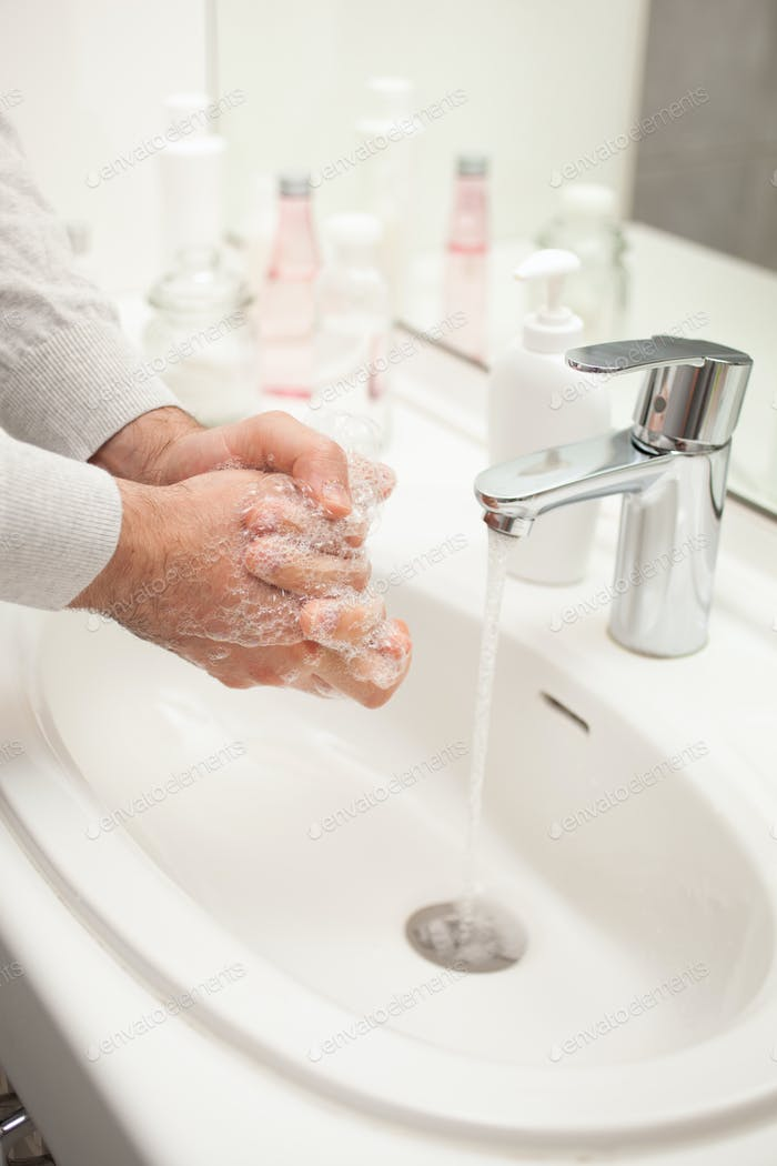 man washing hands with soap at home. coronavirus prevention hand hygiene