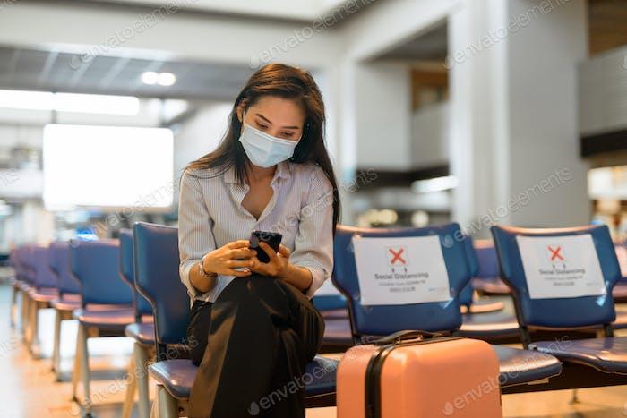 Joven mujer turista asiática con máscara usando teléfono y sentado con distancia en el aeropuerto