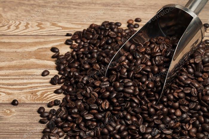 Kaffeebohnen in Löffel auf Holztisch. Platz für Text.