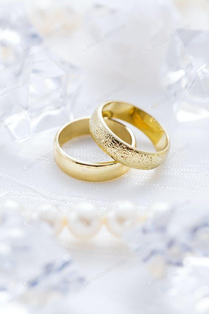 Zwei goldene Ringe mit Perlenhalskette und auf weißem Hintergrund