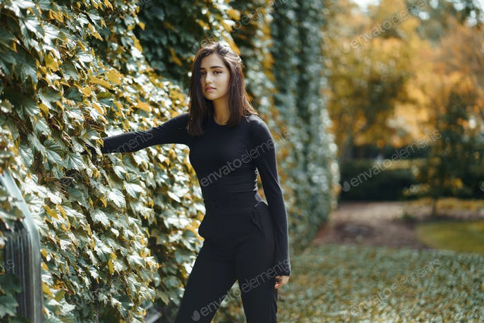 brunette girl walking through the park during autumn