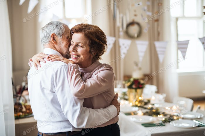 Senior couple standing indoors in a room set for a party, hugging.