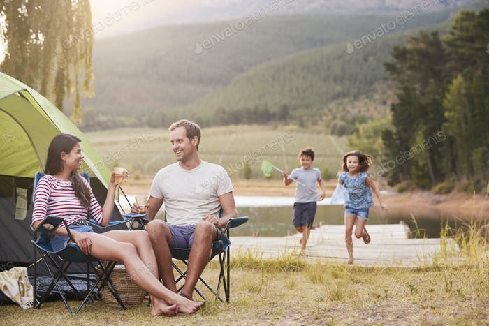 Family Enjoying Camping Vacation By Lake Together