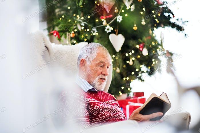 A senior man reading a book at home at Christmas time.