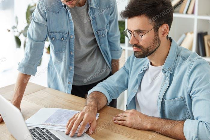 Los colegas masculinos discuten nuevas ideas para aumentar los beneficios, centrados en la computadora portátil, rodeado de