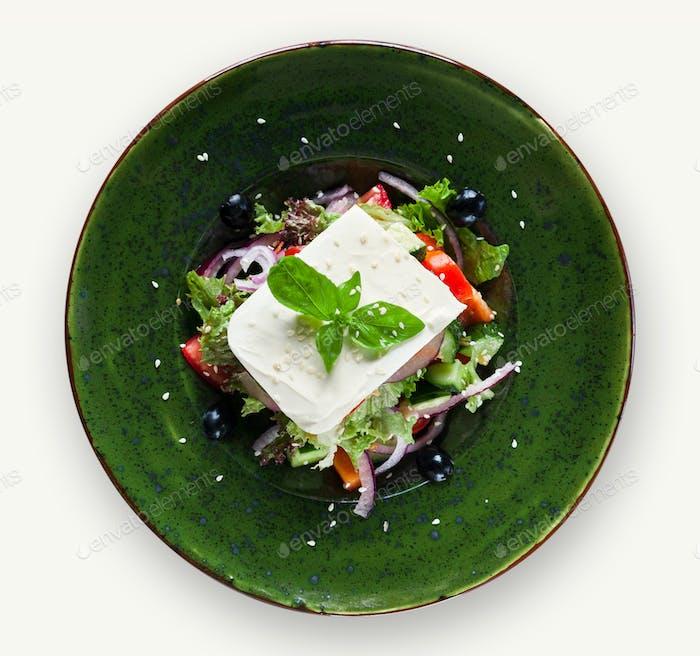Frischer griechischer Salat auf weißem Teller isoliert