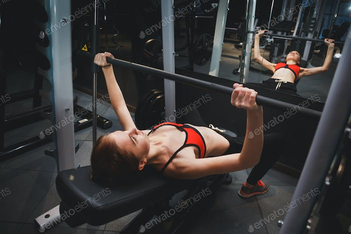 Fitness. Sporty woman exercising with barbell in gym