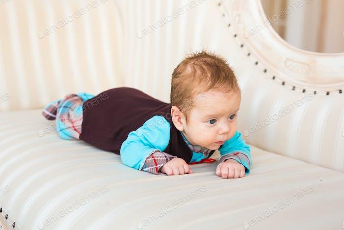Portrait of adorable baby boy lying on tummy