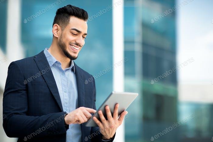 Successful arab guy in formal wear using digital tablet