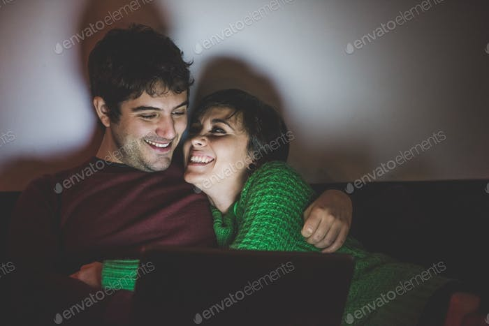 Half length of young handsome man and woman couple sitting on th