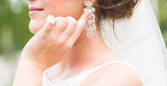 Beautiful bride with fashion earrings, outdoors portrait in park