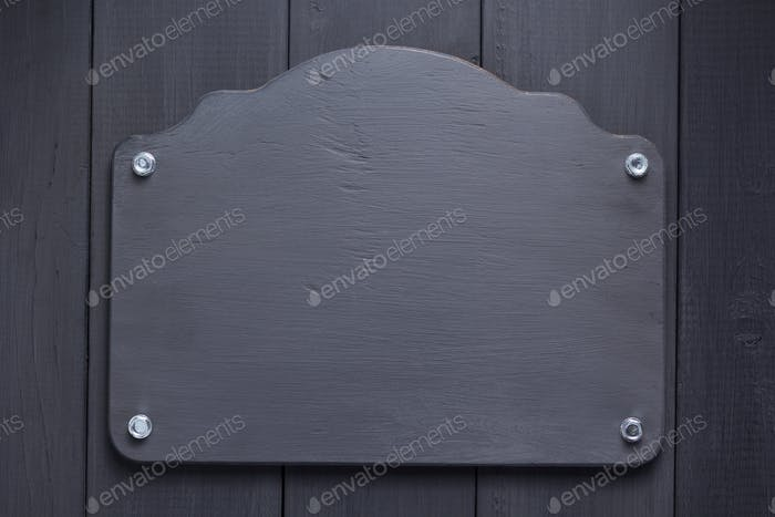 nameplate at black wooden background texture
