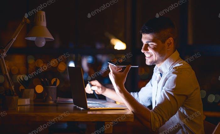 Unternehmer mit Lautsprecher chatten auf Handy über Nacht im Büro arbeiten