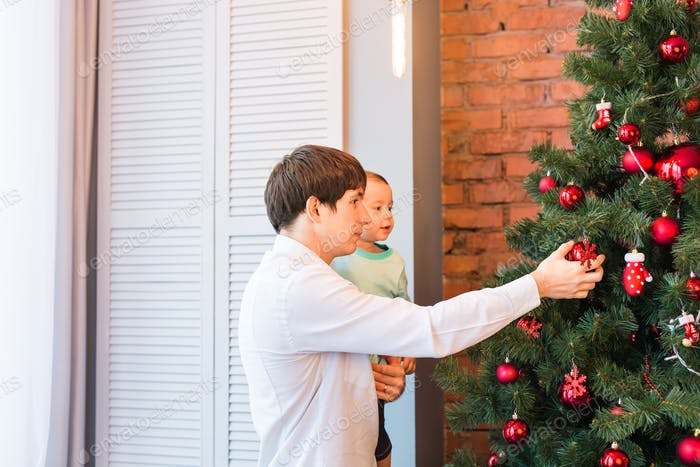 Father and son decorating Christmas tree in the room