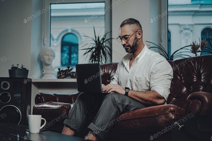 Concentrados en el trabajo hombre caucásico trabajando en la sala de estar