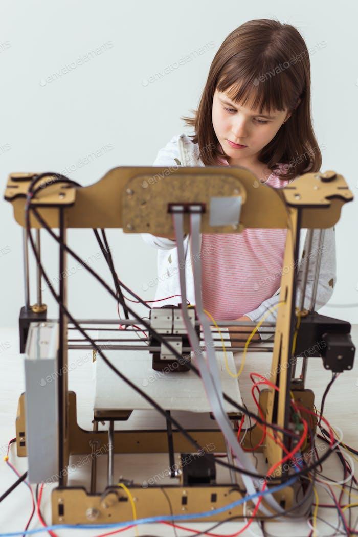 Linda chica con persianas impresas en 3D está viendo su impresora 3D mientras imprime su modelo 3d.