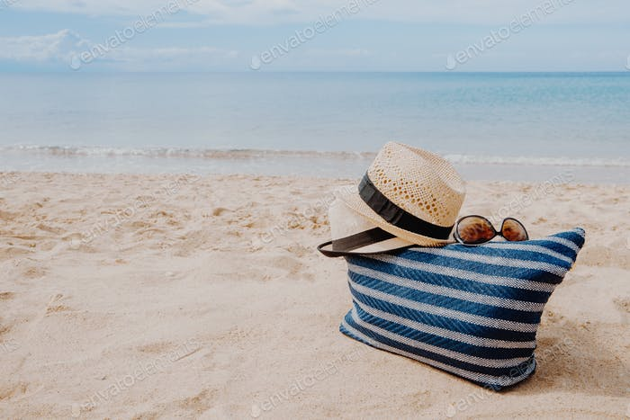 Blue beach bag with sunglasses and hats on the sandy beach with the blue sky background