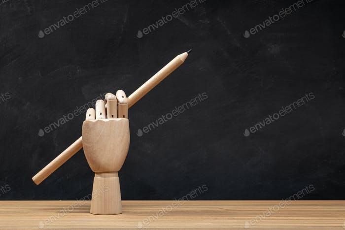 Wooden hand holding a pencil