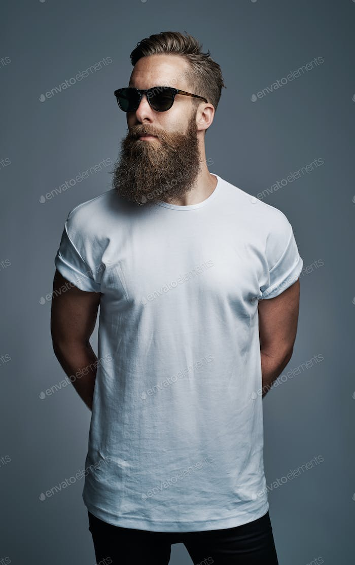 Cool young man with a long beard wearing sunglasses