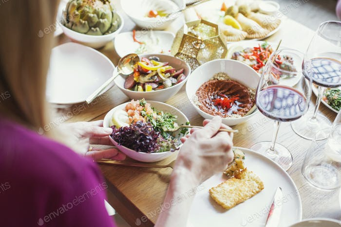 Frau nimmt Essen in Teller im libanesischen Restaurant