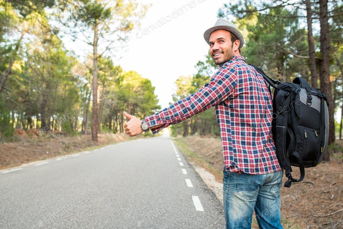 Man hitchhiking with thumbs up in a countryside road