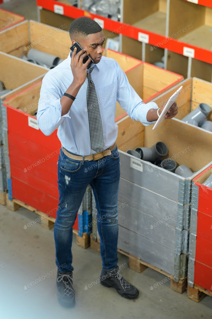 Worker in plumbing supplies shop, using telephone