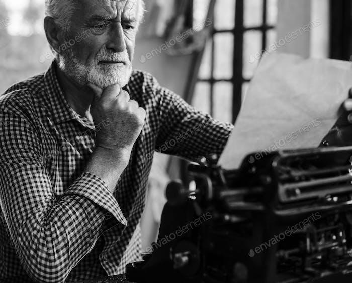 Senior caucasian man using vintage typewriter grayscale