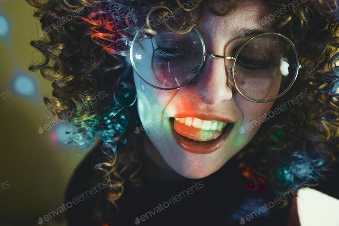 Young woman portrait illuminated by psychedelic lights