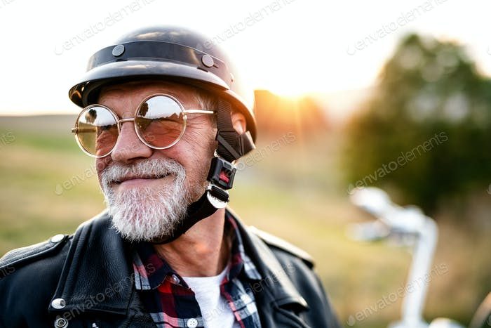 A cheerful senior man traveller with motorbike in countryside, headshot